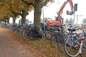 De boel ligt overhoop op het Stationsplein en dus staan de fietsen aan de overzijde onder de kastanjebomen in de berm geparkeerd. Als je pech hebt, ligt je fiets om aan het einde van de dag. (Foto Martin Dekker / Sliedrecht24)